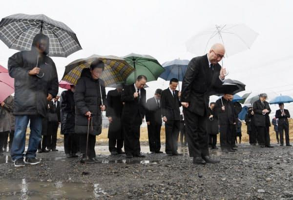 大槌町の旧役場庁舎の跡地で町が主催した追悼式で黙とうする平野公三大槌町長(右手前)ら。4日に建物の解体作業を終え、今年から遺族と合同で行われた(11日午前、岩手県大槌町)