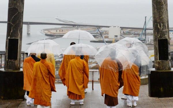 津波が押し寄せた石巻湾を一望する公園で、海に向かって手を合わせる僧侶(11日午前、宮城県石巻市)