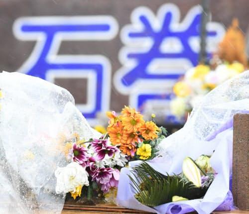 「がんばろう!石巻」の看板前に供えられた花(11日午前、宮城県石巻市)