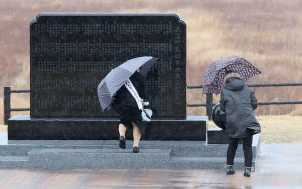 強風に傘を取られながら「浪江町東日本大震災慰霊碑」の前で手を合わせる人たち(11日午前、福島県浪江町)