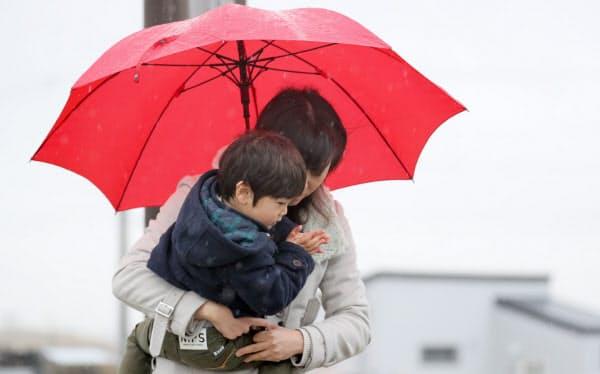 大雨の中、慰霊碑に手を合わせる人たち(11日午前、仙台市若林区)