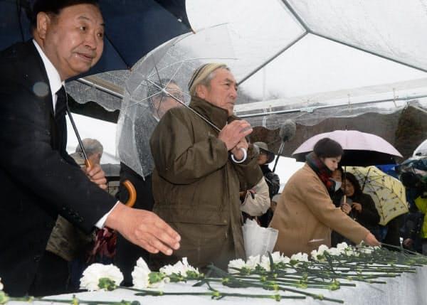 津波で全壊した石巻市立雄勝病院の跡地で献花する人たち(11日午後、宮城県石巻市)