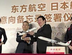 中国東方航空の総経理だった馬須倫氏(左)は中国南方航空集団の経営トップに就いた(2018年8月、日本航空との提携の記者会見)