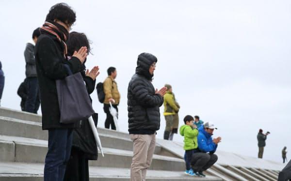 地震発生時刻に黙とうする人たち(11日午後2時46分、仙台市若林区)
