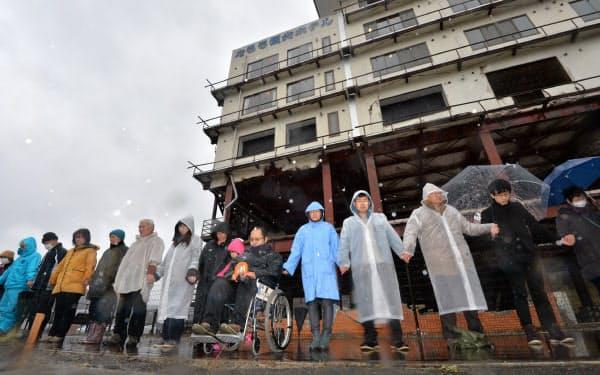 雨が降る中、東日本大震災の発生時刻に合わせ震災遺構の「たろう観光ホテル」の前で手をつないで黙とうする遺族ら(11日午後2時46分、岩手県宮古市)