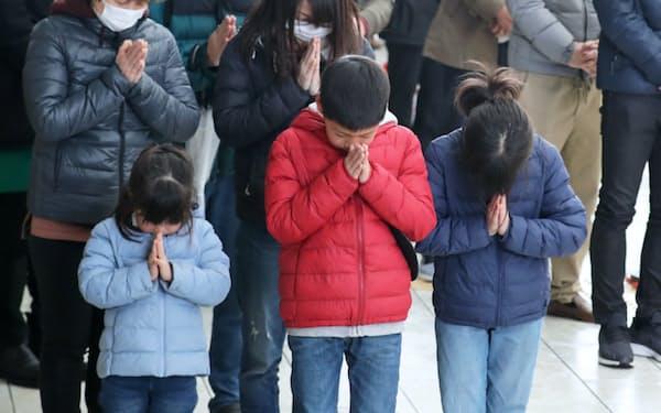新校舎となった閖上小中学校で津波到達時刻に黙とうする児童ら(11日午後、宮城県名取市)