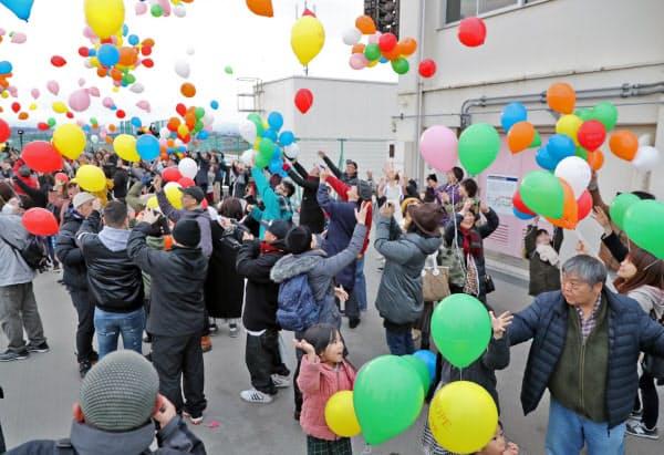 震災遺構として一般公開されている荒浜小学校で風船を飛ばす人たち(11日午後5時15分、仙台市若林区)