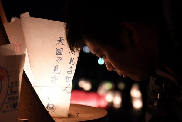 追悼行事でキャンドルに火をともす男性(11日午後7時1分、宮城県石巻市)