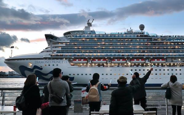 大阪港を出港するクルーズ船。青く光るペンライトを振って見送る(4日)