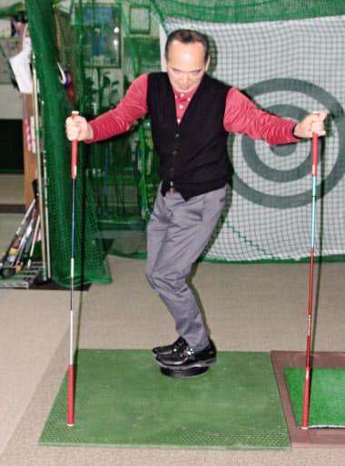 ツイスターに乗り両手を広げる。ゴルフクラブで両手を支え、膝を少し曲げ下半身を右に左にと回転させる。クラブなし、ツイスターなしでもできる