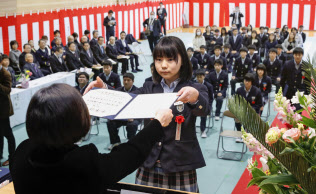 福島県飯舘村で8年ぶりに開かれた飯舘中学校の卒業式で、卒業証書を受け取る生徒(13日午前)=共同