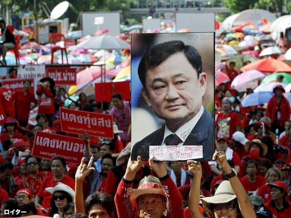 タクシン派はシンボルカラーの赤を身につけ、街頭での大規模なデモ行進をたびたび繰り広げてきた(2012年5月)=ロイター