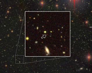 すばる望遠鏡で観測した巨大ブラックホール(点線の四角部分を拡大した白枠の中で、矢印が指している赤い点)=国立天文台提供、共同