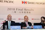 創業家出身のマーリン・スワイヤ会長(中)は事業の先行きに自信を示した(14日、香港)