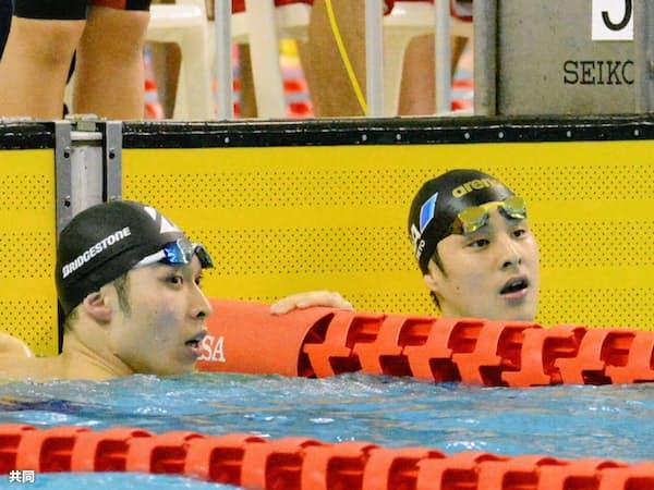 浜名湾選手権の男子200メートル個人メドレーで、レース後にタイムを確認する萩野(左)と瀬戸大也(1月26日)=共同