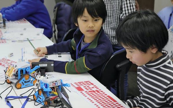 ロボットを動かすプログラムに真剣な表情で取り組む子供たち(東京都中野区)