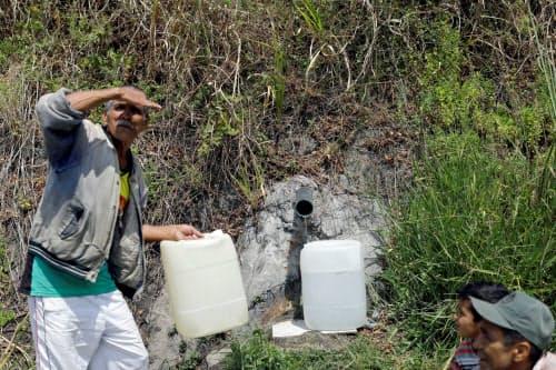 13日、水を求めタンクを持ち並ぶ人々(カラカス)=ロイター