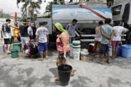 断水のため、バケツを手に給水車に集まる人々(15日、マニラ)=AP
