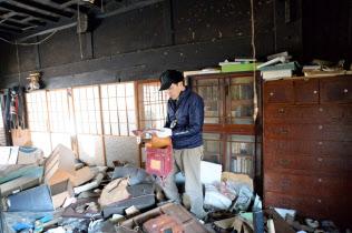 子供のランドセルを見つけた今野さん。イノシシに荒らされた家だが、この場所に戻る思いを抱き続けている(福島県?#31169;?#30010;)