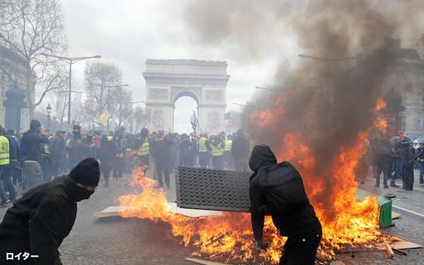 16日、パリ中心部で燃えさかるバリケード=ロイター