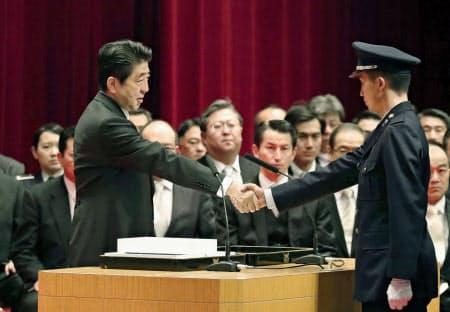 防衛大学校の卒業生と握手する安倍首相(17日午後、神奈川県横須賀市)=共同