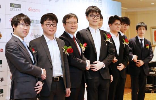記者会見で握手する井山裕太王座(左)らワールド碁チャンピオンシップ2019の出場棋士たち(17日、東京都港区)