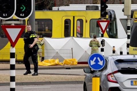 18日、オランダ中部ユトレヒトでの発砲現場を隠す救急隊員ら(AP=共同)
