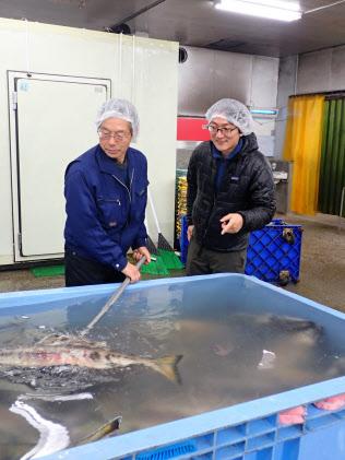 地元水産加工会社を取材?#24037;?#21513;野和也さん(右)(2月16日、岩手県釜石市)