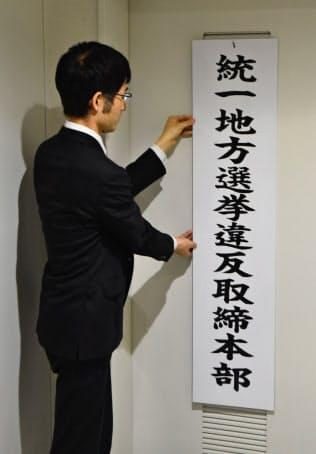 取締本部の看板をかける愛知県警の捜査員(19日、名古屋市中区)