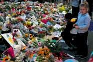 銃乱射事件の犠牲者を悼む人たち(18日、ニュージーランド・クライストチャーチ)