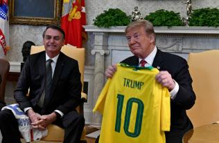 19日、トランプ米大統領(右)にサッカーブラジル代表のユニホームを渡すブラジルのボルソナロ大統(ワシントン)