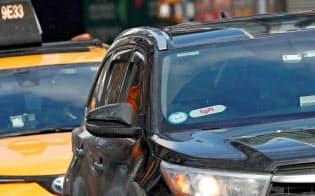 ニューヨークの路上でリフトのロゴをフロントガラスにつけているライドシェアの車がタクシーの前を走っている=ロイター
