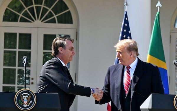 19日、ホワイトハウスで会談を終え握手するブラジルのボルソナロ大統領(左)とトランプ米大統領(ワシントン)