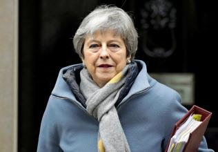 20日、議会へ向かうため官邸を出るメイ英首相(ロンドン)=AP