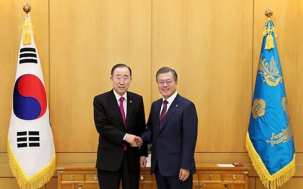 21日、韓国大統領府で文在寅大統領と握手する潘基文前国連事務総長(左)=韓国大統領府提供