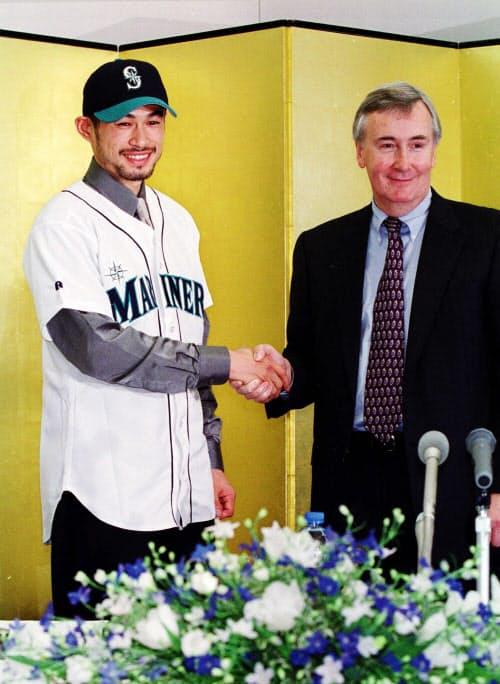 マリナーズへの入団を発表し、ユニホーム姿でハワード・リンカーン最高経営責任者(右)と握手するイチロー外野手(2000年11月19日、京都市南区の任天堂本社)