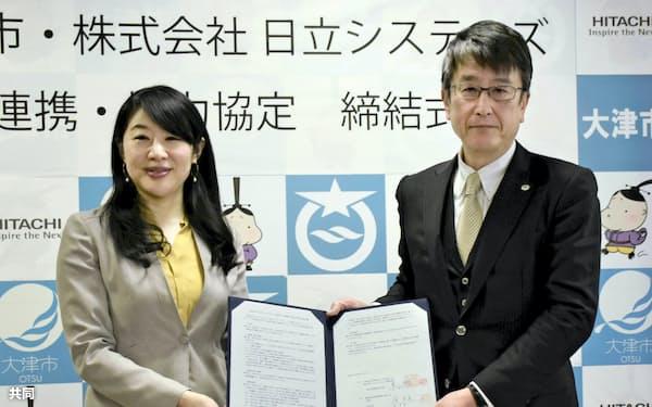 協定書を交わす越直美市長(左)と日立システムズの東浩司・関西支社長(22日、大津市役所)=共同