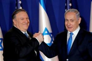 イスラエルを訪問し、ネタニヤフ首相(右)と握手するポンペオ米国務長官(21日、エルサレム)=ロイター