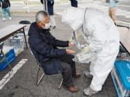 防護服を着た担当者から汚染検査(スクリーニング)を受ける訓練参加者