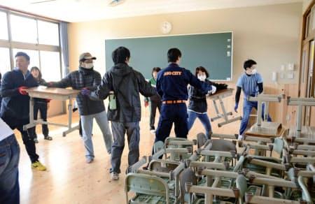 再建された校舎の教室に机などを運び入れる阿蘇西小の関係者ら(24日、熊本県阿蘇市)=共同