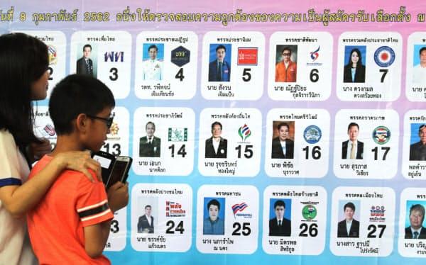 立候補者のボードを見る親子連れ(24日、バンコク)=三村幸作撮影
