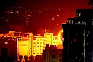 イスラエルによる空爆で炎が上がるガザ地区(25日)=ロイター