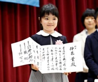 囲碁のプロ初段免状を手に笑顔を見せる仲邑菫さん(26日午後、東京都千代田区の日本棋院)=共同