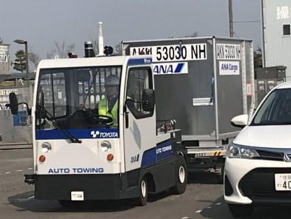 自動走行で貨物コンテナをけん引するトーイングトラクター。レーダーやGPS・自動制御パソコンなどを搭載し、追い越し車両にも的確に対応する(26日、佐賀空港)