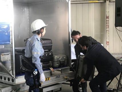 重さ15キロの荷物を慎重に積み込む佐賀県の山口祥義知事(右)。腰への負担を軽減するロボットを装着した女性スタッフ(左)は軽々と処理した