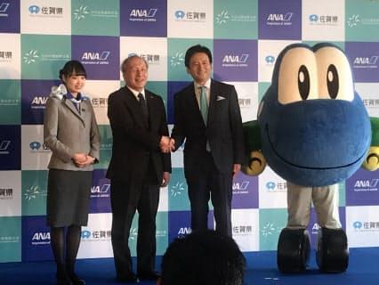 ANAは佐賀空港を拠点に省力化、働き方改革推進に取り組む。握手する同社の清水信三専務(左から2人目)と佐賀県の山口祥義知事