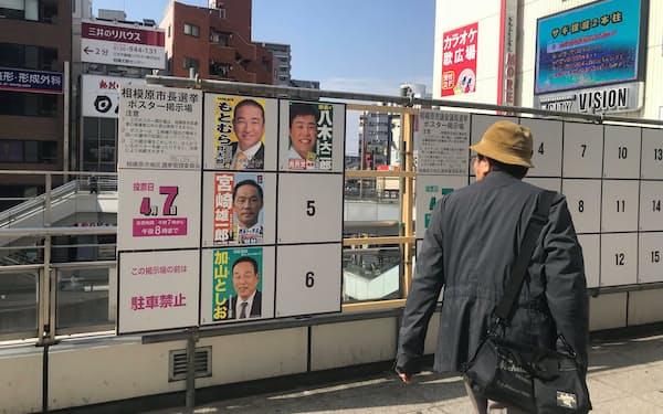 相模原市長選の立候補者のポスターに視線を送る人も