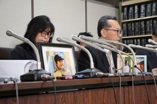 少年の遺影と共に記者会見する両親(3月22日、東京都内)