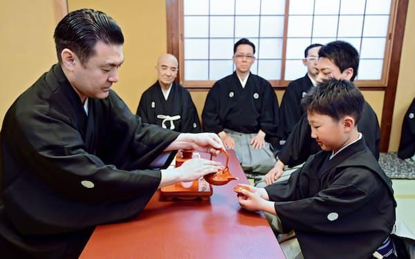 入門の儀式で、竹本織太夫さん(左)から盃を受ける竹本織子太夫さん(28日、大阪市中央区)