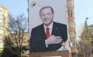 25日、トルコ・イスタンブールに掲げられたエルドアン大統領の巨大な選挙ポスター=共同
